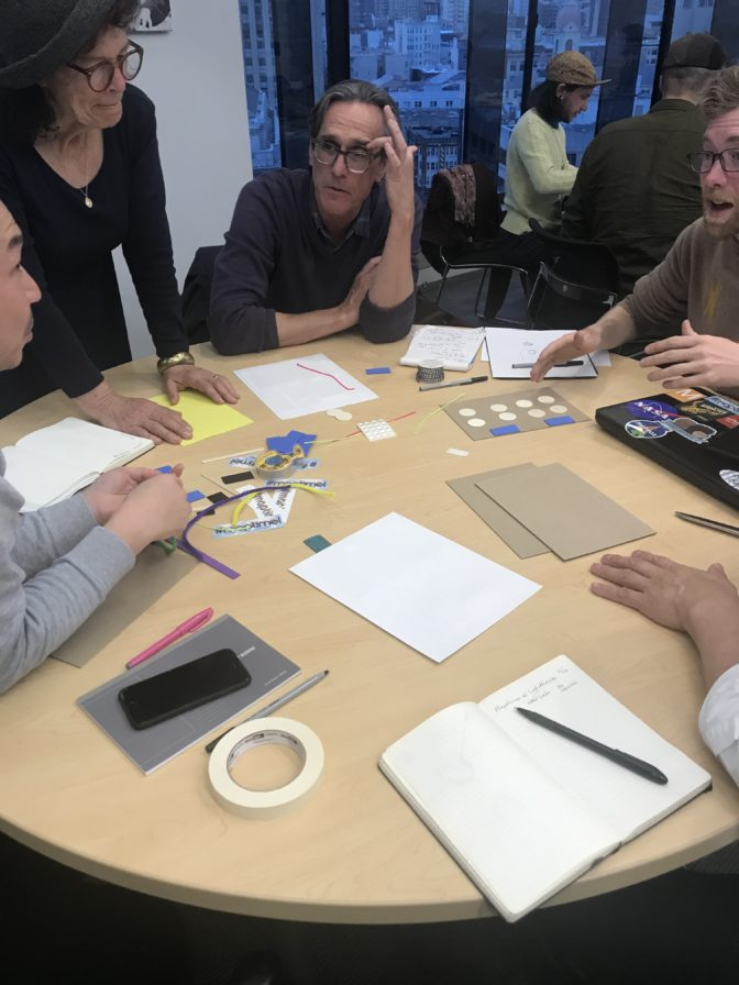 Five Maptimers sit around a circular table while creating their tactile maps. Their tools are pens, paper, foam core, glue, scissors, wiki sticks — anything you can add to paper to build out a tactile layout.